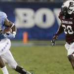 North Carolina's Elijah Hood (34) runs past South Carolina's T.J. Gurley (20) in the second half of an NCAA college football game in Charlotte, N.C., Thursday, Sept. 3, 2015. South Carolina won 17-13. (AP Photo/Chuck Burton)