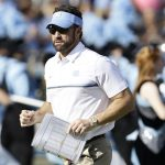 Head coach Larry Fedora runs onto the field