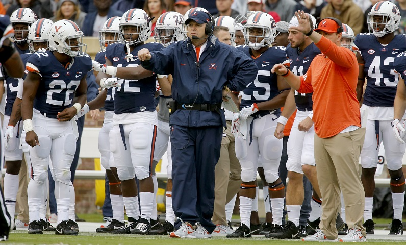 Bronco Mendenhall stands in front of team.